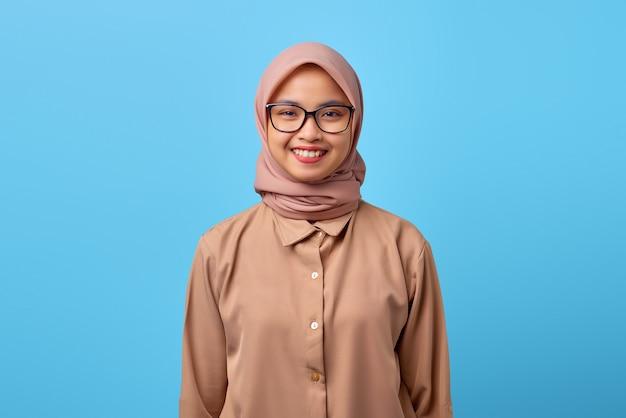Porträt einer lächelnden jungen asiatin mit brille auf blauem hintergrund
