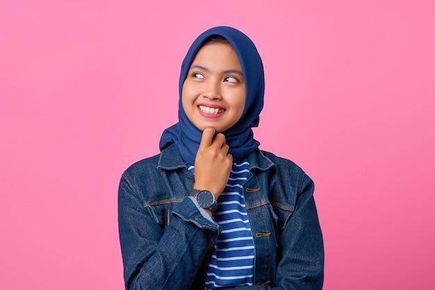 Porträt einer lächelnden jungen asiatin mit hand am kinn und blick zur seite