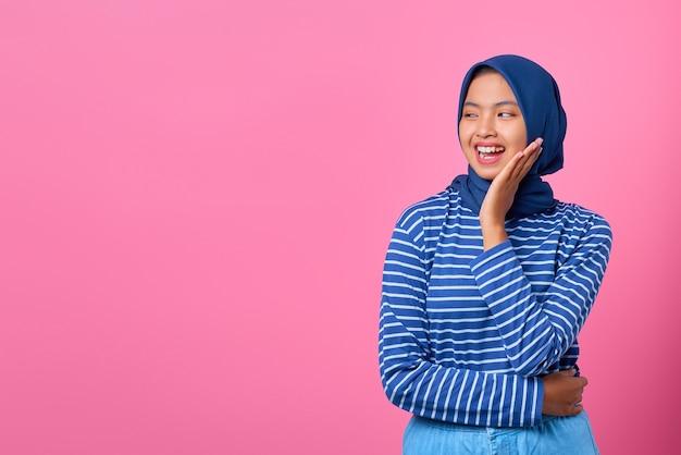 Porträt einer lächelnden jungen asiatin mit hand auf wange und blick zur seite