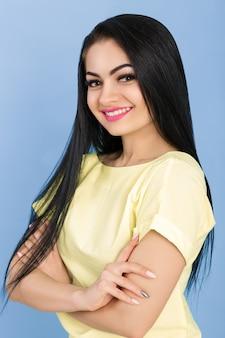 Porträt einer lächelnden jungen brünetten frau im gelben kleid auf blau
