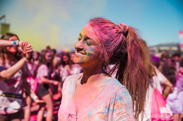 Porträt einer lächelnden jungen frau bedeckt mit holi farbe