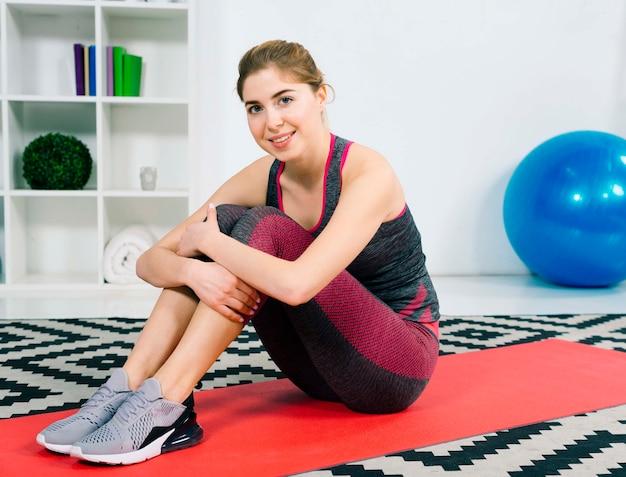 Porträt einer lächelnden jungen frau der eignung in der sportkleidung, die auf rotem teppich sitzt