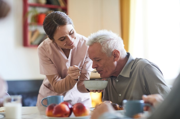 Porträt einer lächelnden jungen frau, die älteren patienten beim abendessen im pflegeheim-kopierraum hilft