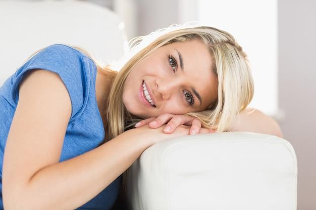 Porträt einer lächelnden jungen frau, die auf sofa sitzt