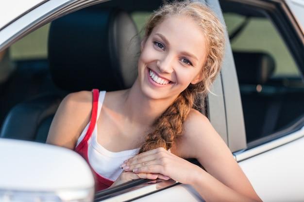 Porträt einer lächelnden jungen frau, die aus dem fenster ihres autos schaut