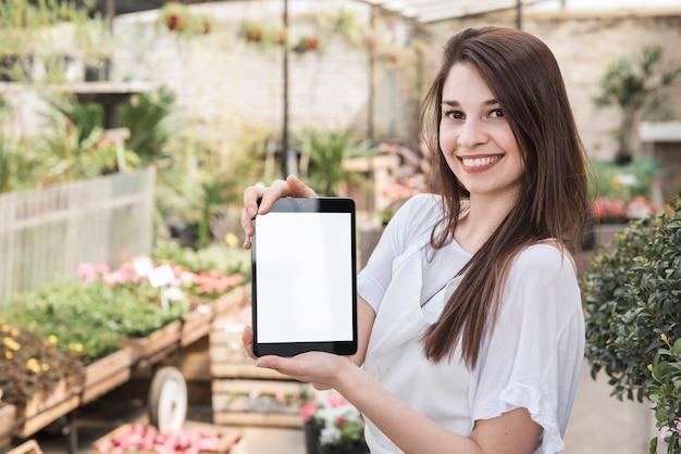 Porträt einer lächelnden jungen frau, die digitale tablette mit leerem weißem bildschirm hält