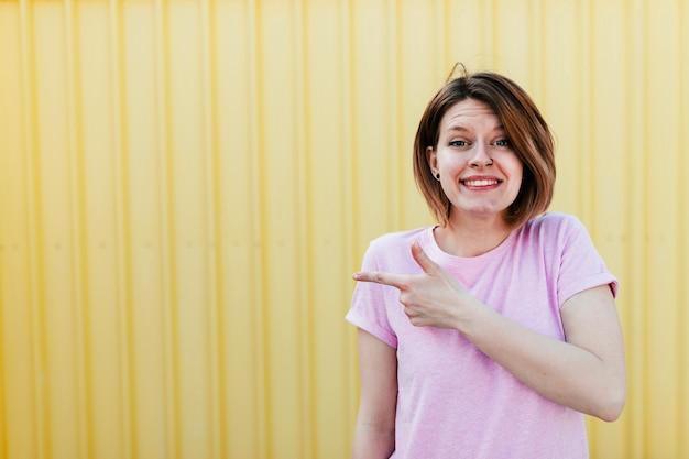 Porträt einer lächelnden jungen frau, die finger gegen gewölbte gelbe blechtafel zeigt