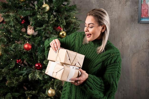 Porträt einer lächelnden jungen frau, die geschenke betrachtet