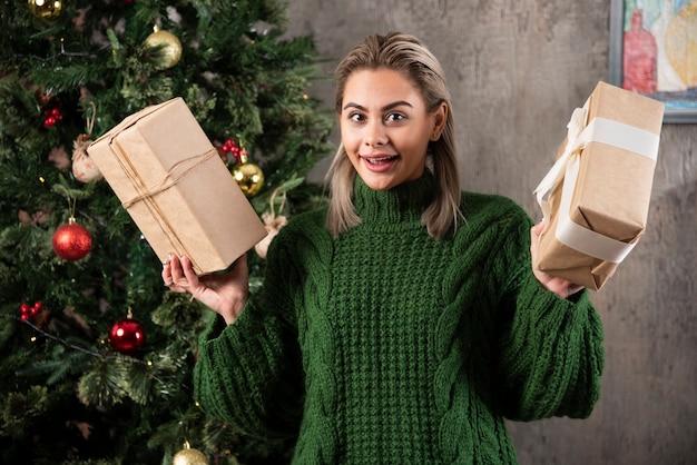 Porträt einer lächelnden jungen frau, die geschenke hält