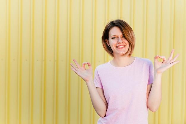 Porträt einer lächelnden jungen frau, die handzeichen gegen gelben fensterladenhintergrund zeigt