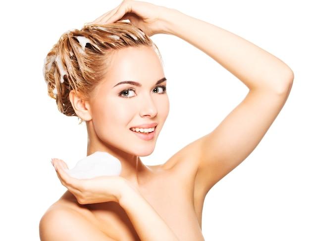 Porträt einer lächelnden jungen frau, die ihre haare auf einem weiß wäscht