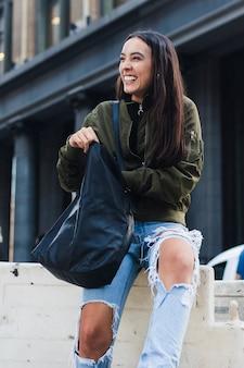 Porträt einer lächelnden jungen frau, die in der blauen handtasche schaut