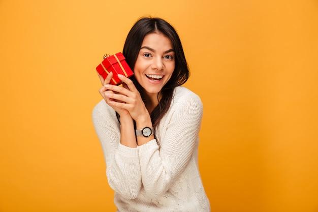 Porträt einer lächelnden jungen frau, die kleine geschenkbox hält