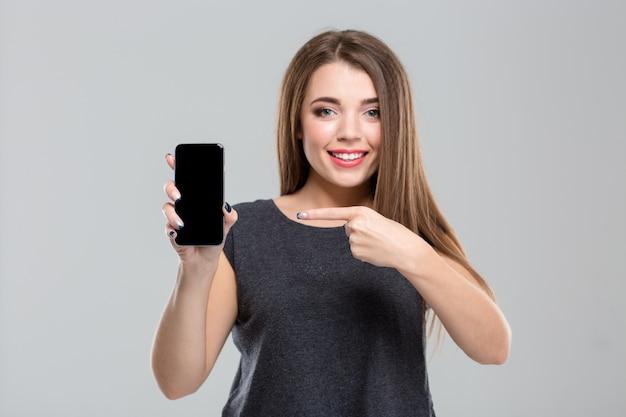 Porträt einer lächelnden jungen frau, die mit dem finger auf einen leeren smartphone-bildschirm zeigt, isoliert auf weißem hintergrund