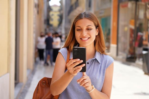 Porträt einer lächelnden jungen frau, die mit einem smartphone auf der straße geht