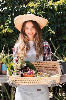 Porträt einer lächelnden jungen frau, die topfpflanzen im korb hält