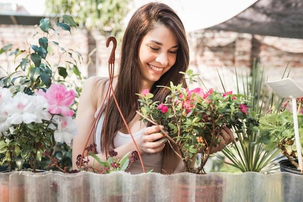 Porträt einer lächelnden jungen frau, die um blühender pflanze im garten sich kümmert