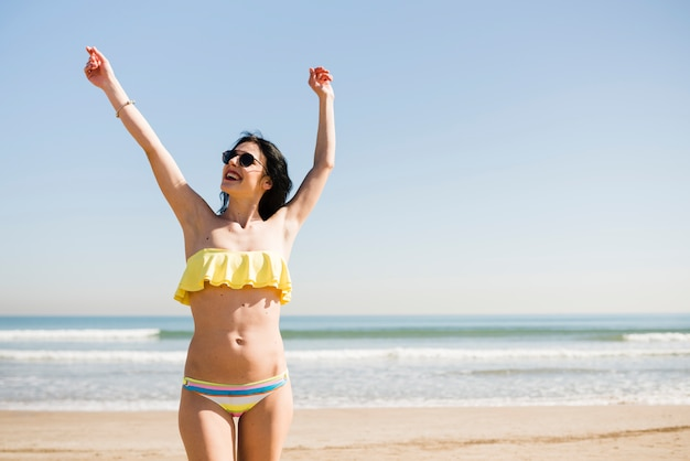 Porträt einer lächelnden jungen frau im bikini, der nahe dem meer gegen blauen himmel am strand steht