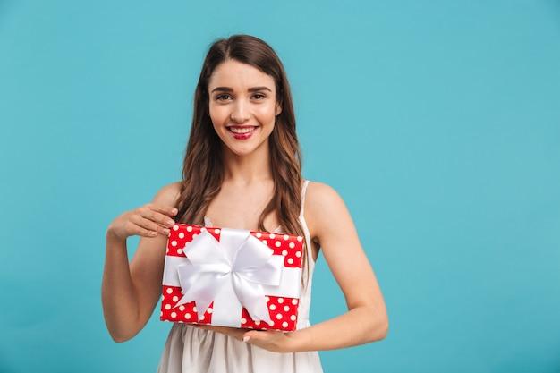 Porträt einer lächelnden jungen frau im sommerkleid, die eine geschenkbox hält