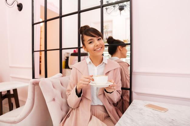 Porträt einer lächelnden jungen frau in der rosa jacke, die kaffee trinkt