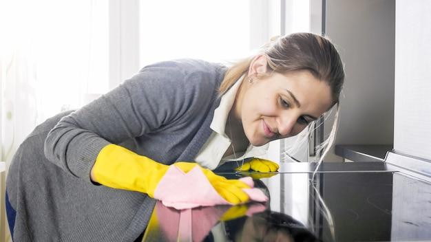 Porträt einer lächelnden jungen frau in gummihandschuhen, die küchenarbeitsplatte und herd säubert und wäscht.