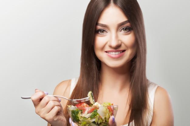 Porträt einer lächelnden jungen frau mit vegetarischem gemüsesalat. gesunder lebensstil. gesundes essen.
