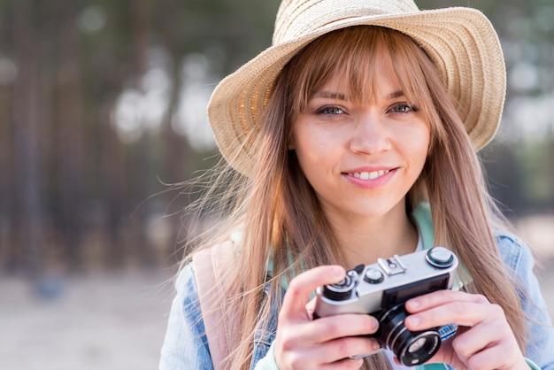 Porträt einer lächelnden jungen frau, welche die kamera in der hand betrachtet kamera hält
