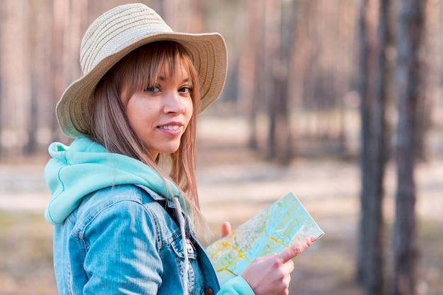 Porträt einer lächelnden jungen frau, welche die karte in der hand betrachtet kamera hält