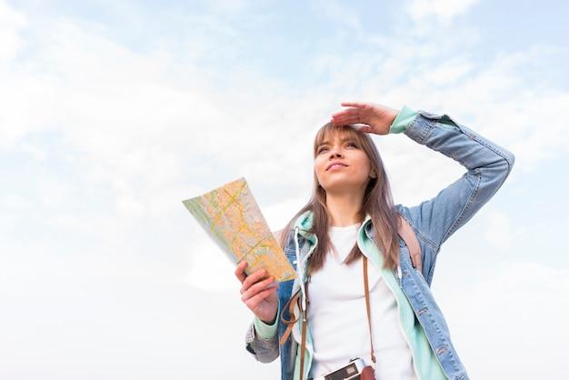 Porträt einer lächelnden jungen frau, welche die karte in der hand schützt ihre augen gegen himmel hält