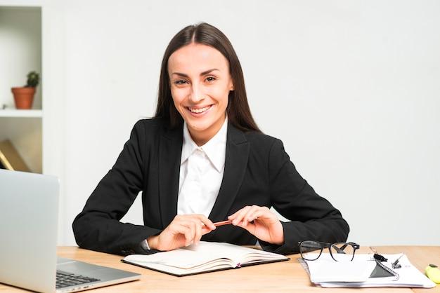 Porträt einer lächelnden jungen geschäftsfrau, die am schreibtisch mit bleistift und tagebuch sitzt