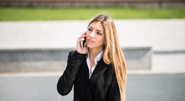 Porträt einer lächelnden jungen geschäftsfrau, die am telefon spricht