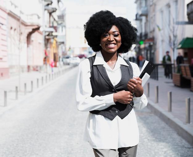 Porträt einer lächelnden jungen geschäftsfrau, die das klemmbrett betrachtet kamera hält