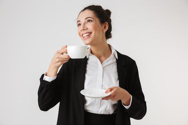 Porträt einer lächelnden jungen geschäftsfrau, die tee trinkt