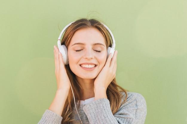 Porträt einer lächelnden jungen hörenden frau die musik auf kopfhörer mit ihrem auge schloss gegen tadellosen grünen hintergrund