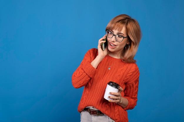 Porträt einer lächelnden jungen lässigen frau, die auf handy lokalisiert über blauem hintergrund spricht.