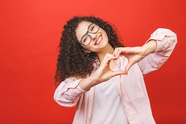 Porträt einer lächelnden jungen lockigen frau, die herzgeste mit zwei händen zeigt und kamera lokalisiert über rotem hintergrund betrachtet.