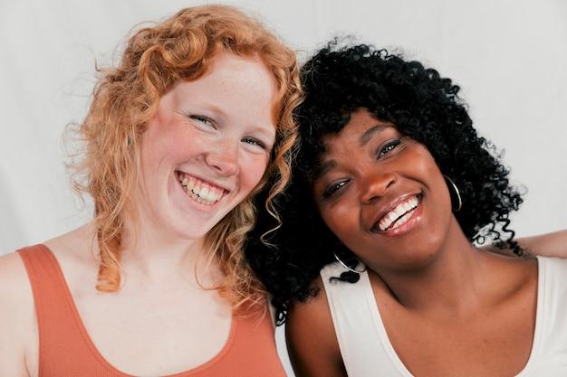 Porträt einer lächelnden jungen multi ethnischen freundin, die kamera betrachtet
