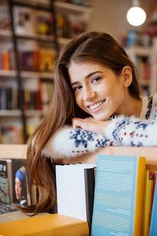 Porträt einer lächelnden jungen studentin in der bibliothek