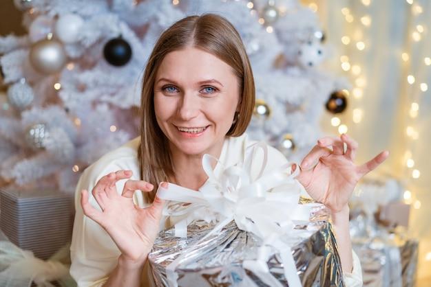 Porträt einer lächelnden kaukasischen frau, die ein leichtes kleid trägt und eine silberne geschenkbox in der nähe eines baumes hält...