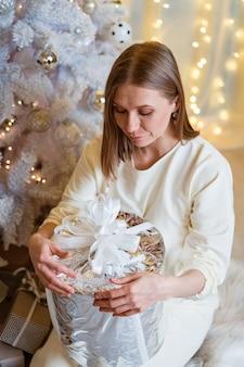 Porträt einer lächelnden kaukasischen frau, die eine silberne geschenkbox in der nähe eines baumes hält, öffnet eine junge frau ihre präsentation