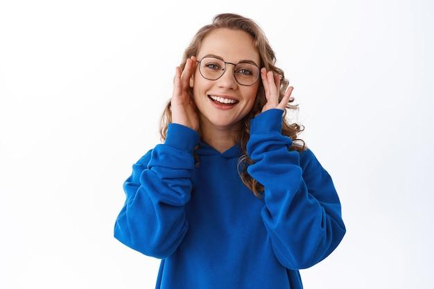 Porträt einer lächelnden modernen studentin, brille aufsetzen und lächeln, brille und blauen hoodie tragend, über weißer wand stehend