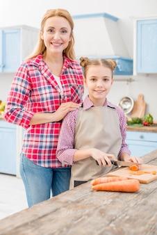 Porträt einer lächelnden mutter und der tochter, welche die karotte mit messer in der küche schneiden