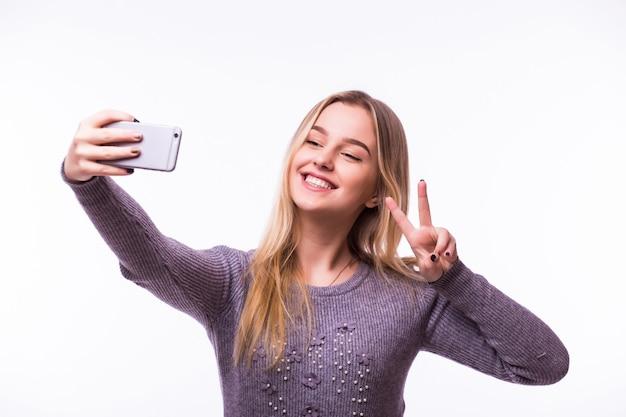 Porträt einer lächelnden niedlichen frau, die selfie-foto auf smartphone lokalisiert auf einer weißen wand macht