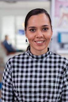 Porträt einer lächelnden patientin, die auf die kamera schaut, die auf einem stuhl im wartezimmer der stomatologischen...