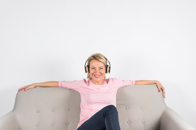 Porträt einer lächelnden reifen frau, die auf dem sofa betrachtet kamera gegen weißen hintergrund sitzt