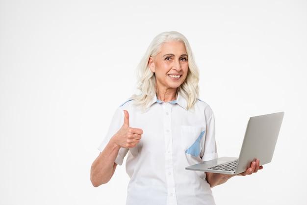 Porträt einer lächelnden reifen frau, die laptop-computer hält