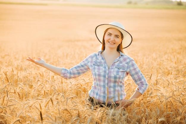 Porträt einer lächelnden schönen bäuerin mit ausgestreckter handfrau am weizenfeld im sommer da...