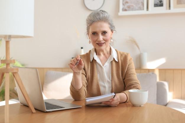 Porträt einer lächelnden schönen frau mittleren alters, die in die kamera schaut, videoanrufe, vorstellungsgespräche oder online-dating macht.