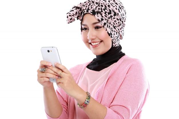 Porträt einer lächelnden schönen muslimischen frau, die mit ihrem smartphone eine sms sendet