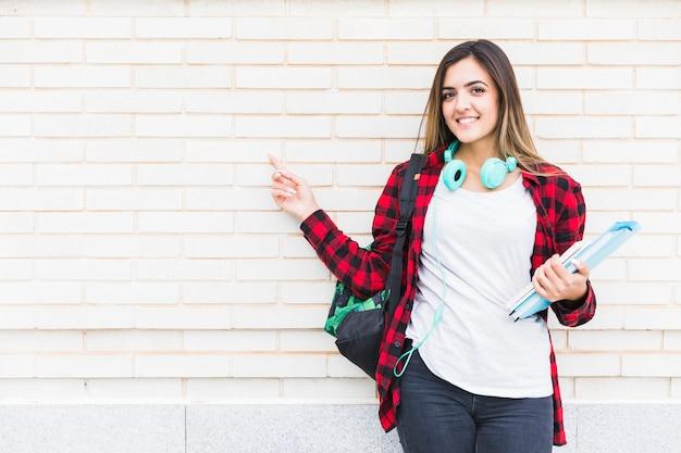 Porträt einer lächelnden schönen studentin, die bücher hält und rucksack auf der schulter zeigend ihren finger gegen weiße backsteinmauer trägt
